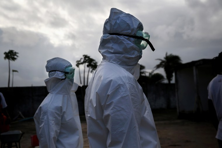 A burial team from the Liberian Ministry of Health prepares to unload the bodies of Ebola victims onto a funeral pyre at a crematorium on Aug. 22, 2014 in Marshall, Liberia.
