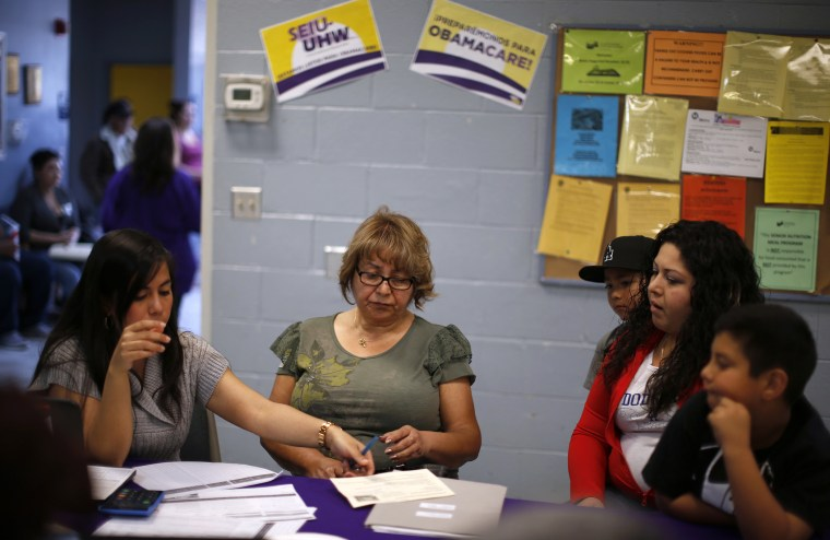 Maria Renteria (L), explains health insurance options to Manuela Ruiz and her daughter at an enrollment event in Cudahy, California March 27, 2014.