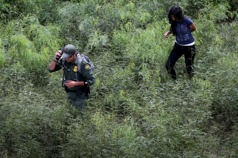 A U.S. Border Patrol escorts an undocumented immigrant, her arm handcuffed behind her back, after detaining her in the brush on Sept. 11, 2014 near Falfurrias, Texas.