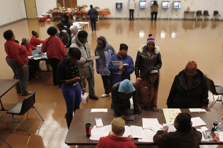 Voters wait in line to register before they can cast their ballots in the U.S. presidential election on Nov. 6, 2012 in Milwaukee, Wisc.