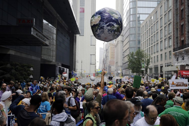 A man throws an earth balloon into the air as people fill 58th Street between 8th and 9th Avenue before a global warming march in New York Sunday, Sept. 21, 2014. (Photo by Mel Evans/AP)