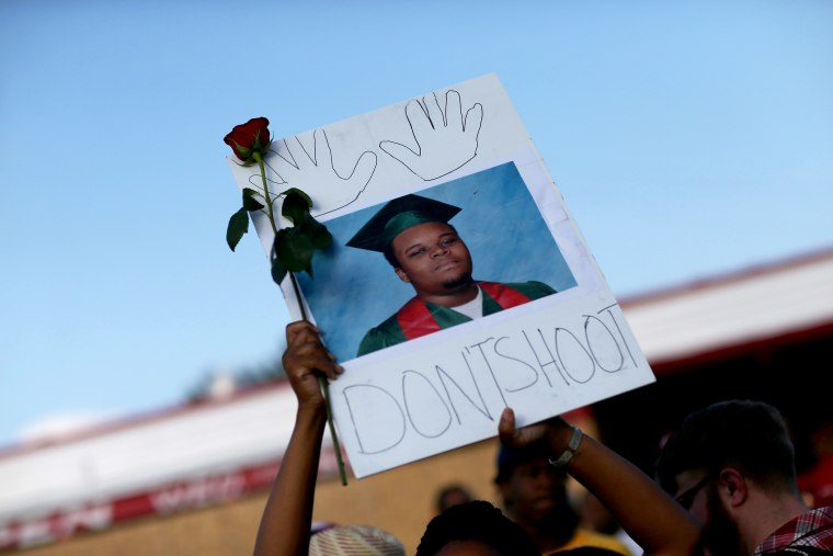 """A demonstrator holds a sign reading, \""""Dont Shoot\"""", with a picture of Michael Brown on Aug. 17, 2014 in Ferguson, Mo. (Photo by Joe Raedle/Getty)"""