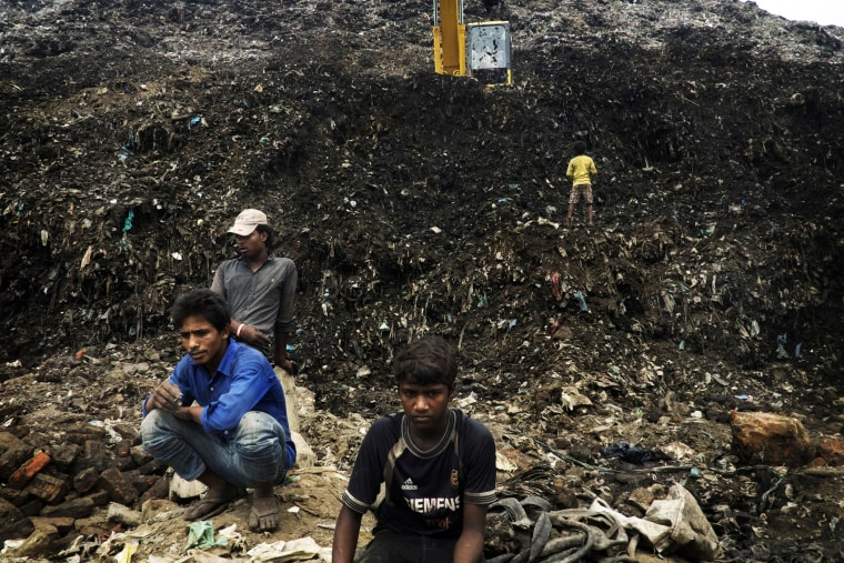 A group of extremely poor people trying to recover anything of value from an immense dump in the center of Delhi, India, Aug. 2014.