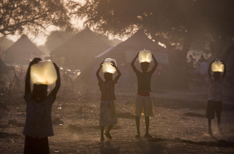 Minkaman, Awerial County, South Sudan where children collect water for their families in the half-light of sunset.