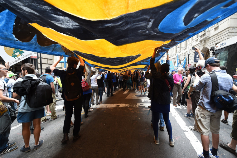 """Protestors make their way up Broadway as they take part in the \""""Flood Wall Street\"""" demonstrations on Sept. 22, 2014, preceding the United Nations's \""""Climate Summit 2014: Catalyzing Action\"""" in New York, N.Y. (Photo by Timothy A. Clary/AFP/Getty)"""
