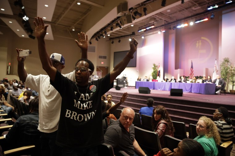 Attendees raise theirs arms during a public comments portion of a meeting of the Ferguson City Council, in Ferguson, Mo. on Sept. 9, 2014.