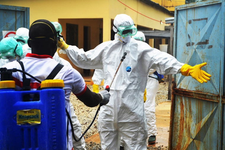 Guinea's Red Cross health workers wear protective suits prepare to carry the body of a victim of Ebola near the hospital Donka in Conakry, Sept. 14, 2014.