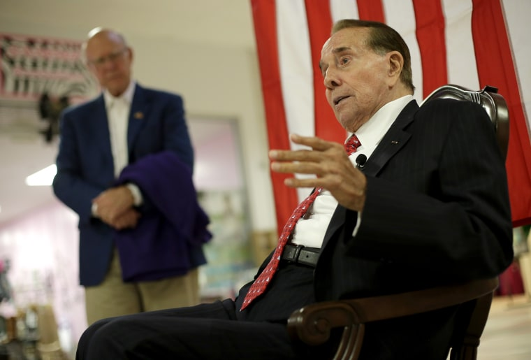 Republican Sen. Pat Roberts listens while former Senate Majority Leader Bob Dole, right, speaks during a campaign stop at a mall in Dodge City, Kan, Monday, Sept. 22, 2014.