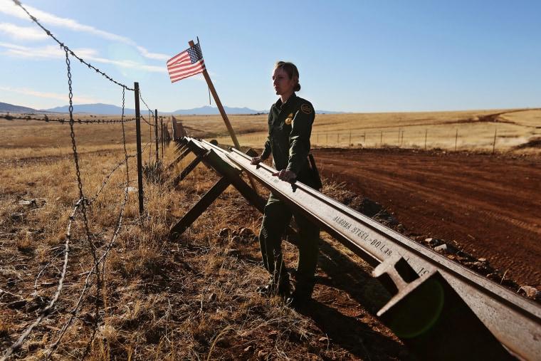 A U.S. Border Patrol agent looks into Mexico from the U.S.-Mexico border on February 26, 2013 near Sonoita, Arizona.