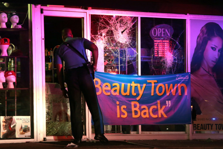 A Missouri Highway Patrol trooper looks inside the vandalized Beauty Town store on West Florissant Avenue in Ferguson late Tuesday, Sept. 23, 2014.