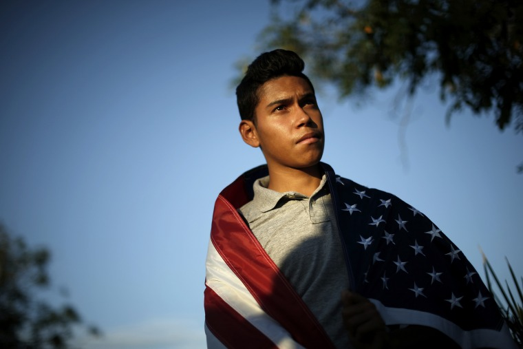 William Bello, 16, listens to speakers at a vigil in support of refugee children and their families in Murrieta, Calif. on July 9, 2014.