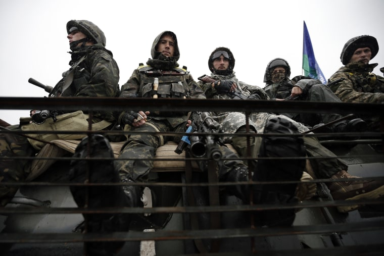 Ukrainian servicemen sit on their armoured vehicle near the village of Luhanske