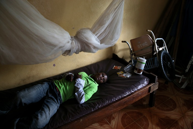 John Karpee, 24, lies in an observation room at a government clinic on Aug. 24, 2014 in Dolo Town, Liberia.