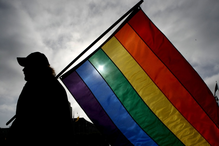 A man holds a gay pride flag. (Photo by Justin Sullivan/Getty)