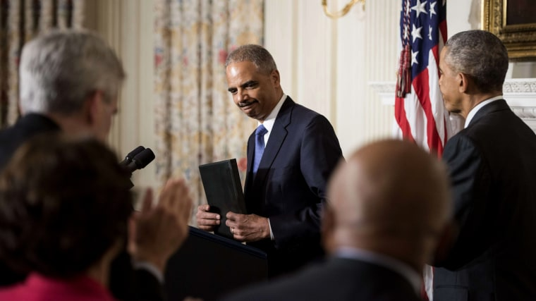 US President Barack Obama (R) listens while US Attorney General Eric H. Holder, Jr., speaks during an event in the State Dining Room of the White House Sept. 25, 2014 in Washington, DC.