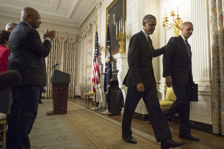 US President Barack Obama (2-R) and US Attorney General Eric Holder (R) walk away from the podium after they delivered remarks on Holder's resignation, at the White House, in Washington on Sept. 25, 2014.