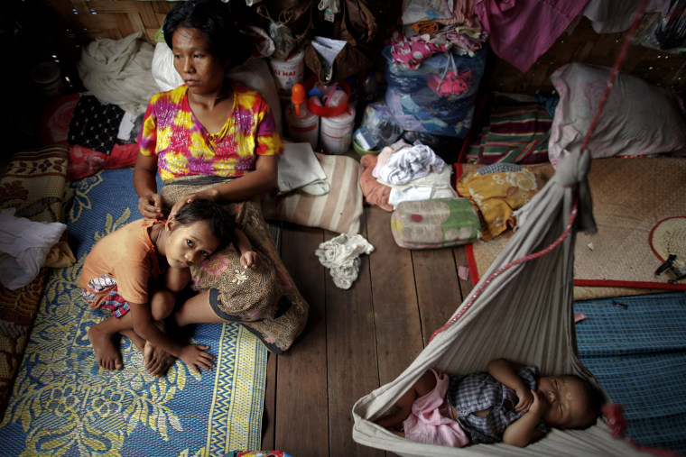HIV-positive Ma Mon comforts her non-positive daughter Myat Noe Thu as her HIV-positive son Ei Ei Phyu sleeps in a hammock at the HIV/AIDS hospice founded by a member of the National League for Democracy (NLD) party in the suburbs of Yangon. Myanmar on Ma