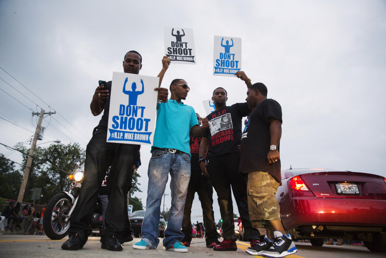 Demonstrators gesture and chant as they continue to react to the shooting of Michael Brown in Ferguson, Missouri August 17, 2014.