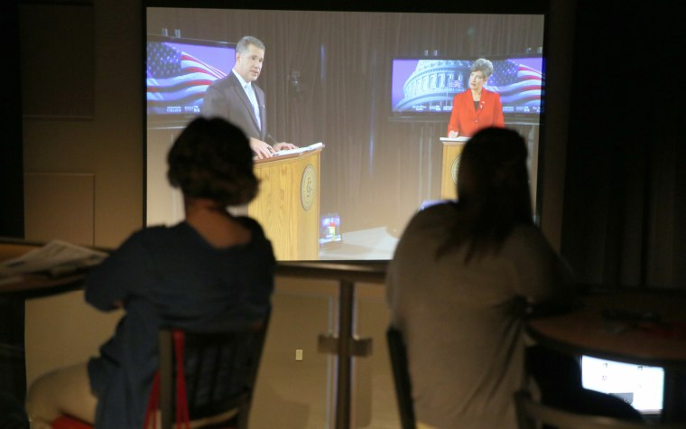 People watch the debate between Senate candidates Rep. Bruce Braley, D-Iowa, Republican senatorial candidate State Sen. Joni Ernst, in the balcony of the...
