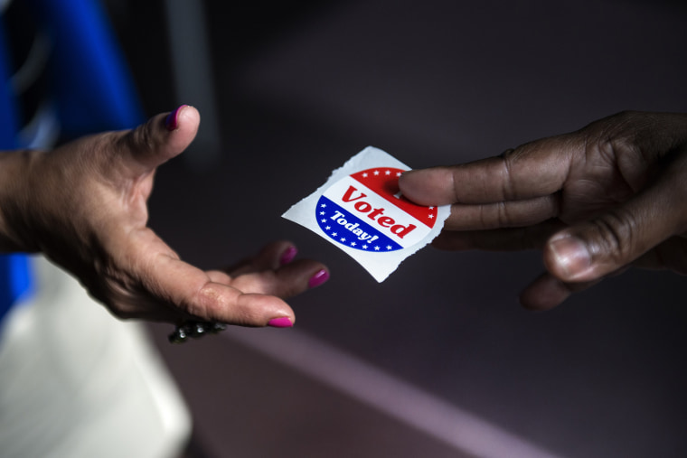 "A poll worker hands out ""I Voted Today"" stickers on October 22, 2012."