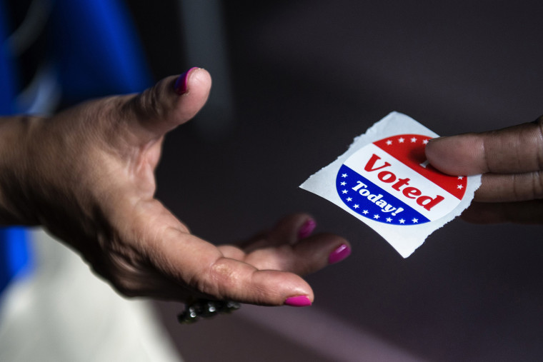 """A poll worker hands out \""""I Voted Today\"""" stickers on October 22, 2012"""