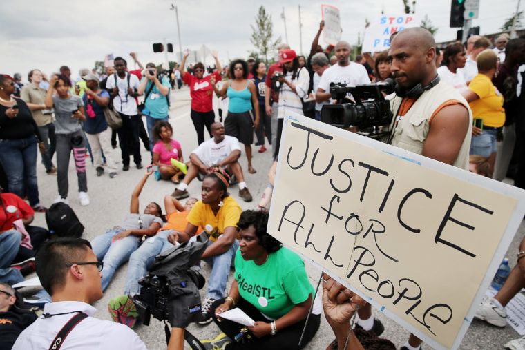 Demonstrators sit in the street after police prevented them from gaining access to Interstate Highway 70 during a protest on Sept. 10, 2014 near Ferguson, Mo.