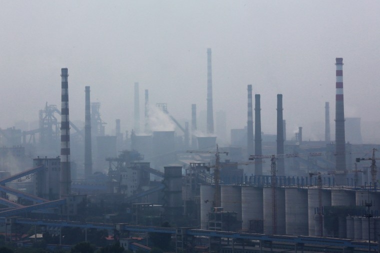 A steel factory is seen in smog during a hazy day in Anshan, Liaoning province, China on June 29, 2014.