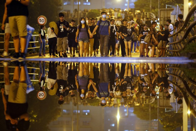 Protesters walk along a street as they block an area near the government headquarters building in Hong Kong
