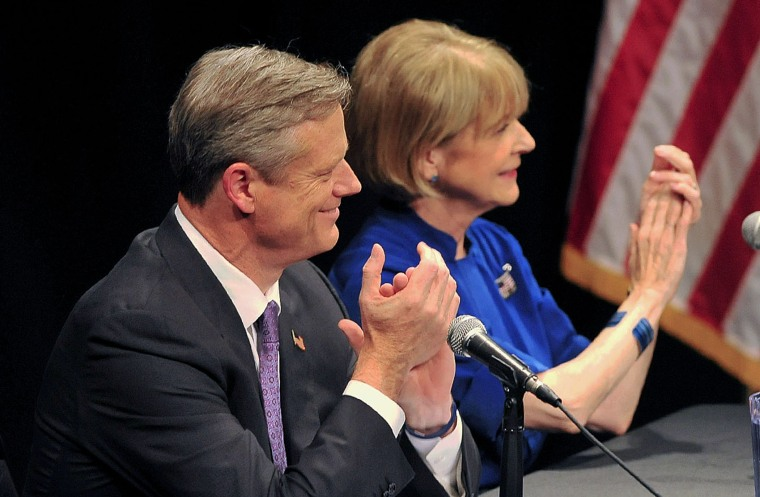 Mass. Republican nominee for governor Charlie Baker, left, and Democratic nominee Martha Coakley applaud at the start of a debate in Springfield, Mass.,...