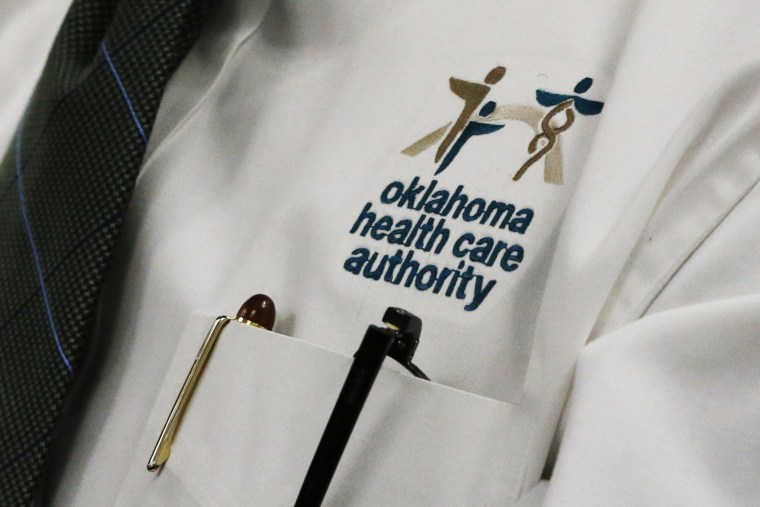 An audience member wears an Oklahoma Health Care Authority shirt during an OHCA board meeting in Oklahoma City, July 1, 2014.