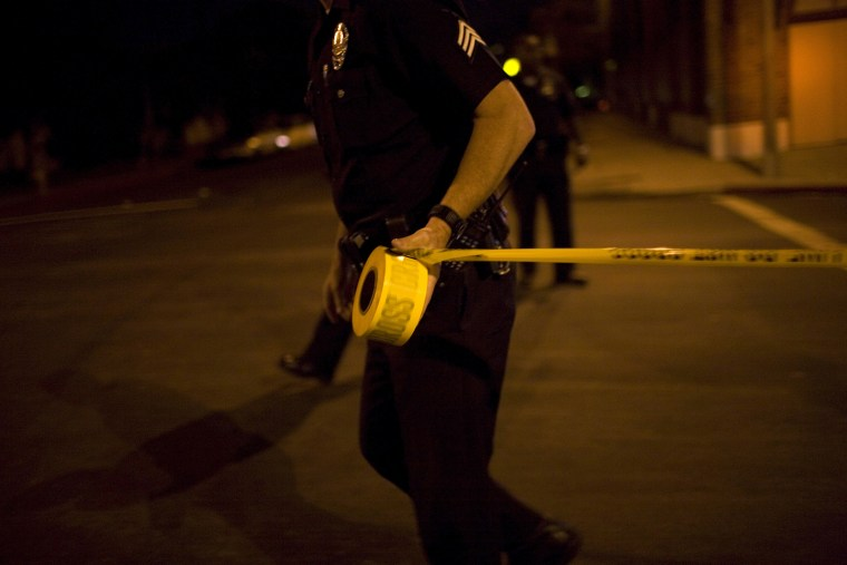 Los Angeles Police Department officers tape off a Crime Scene Investigation area.