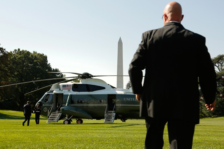 A Secret Service agent watches as U.S. President Barack Obama boards the Marine One helicopter, Aug. 26, 2014.