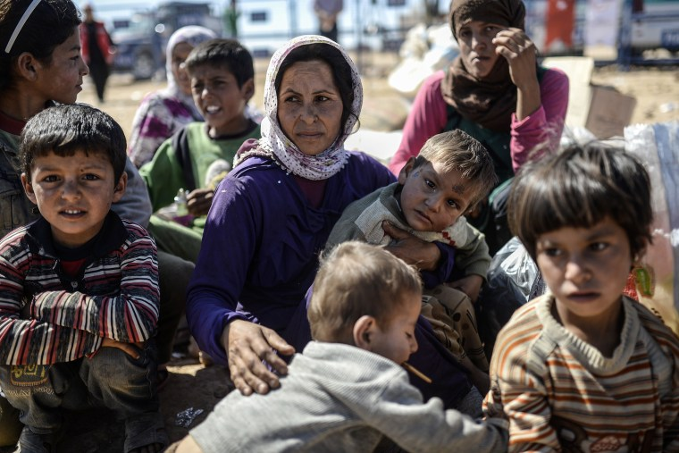 Syrian Kurds wait near the southeastern town of Suruc in the Sanliurfa province after crossing the border between Syria and Turkey on Oct. 1, 2014.