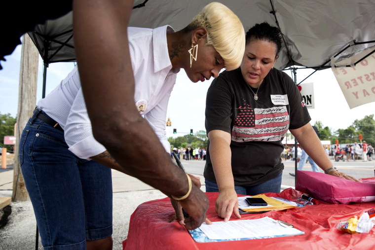 Shiron Hagens, right, helps resident Rita Foley register to vote at a rally in Ferguson, Mo., Aug. 30, 2014.