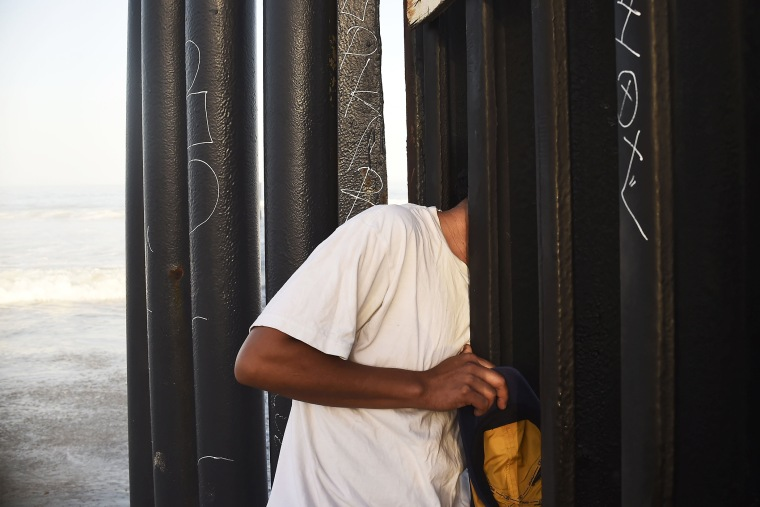 A man looks through the fence that divides Mexico and the US, in Tijuana, Baja California State, Mexico, on September 17, 2014.