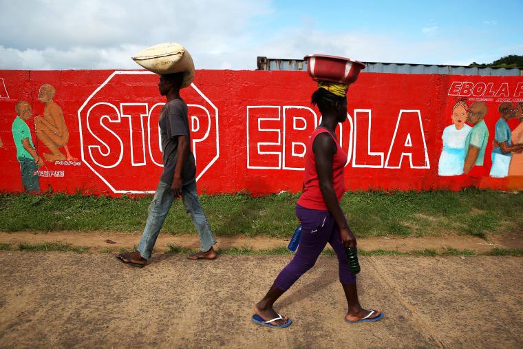 People pass an Ebola awareness mural on October 2, 2014 in Monrovia, Liberia.