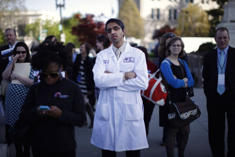 Doctor Vivek Murthy stands among other bystanders outside the Supreme Court in Washington, March 26, 2012.
