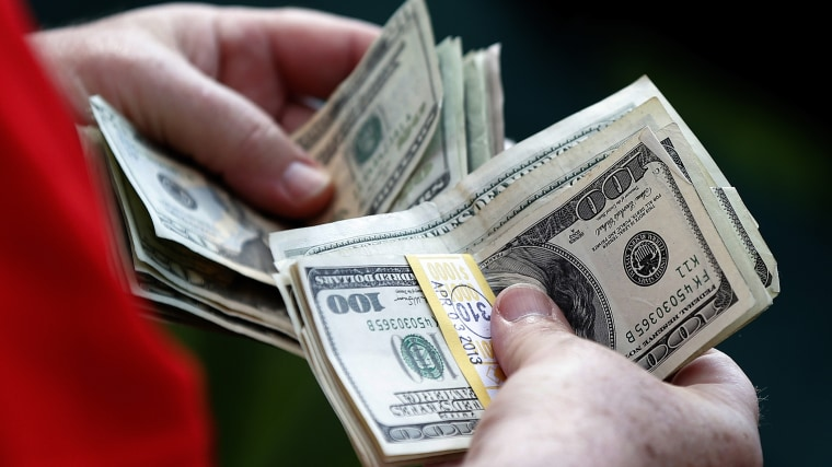 A man counts his money. (Photo by Phil Noble/Reuters)