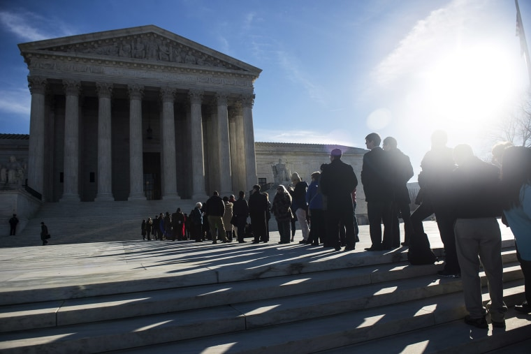 People wait in line to enter the U.S. Supreme Court on the first day of January sessions in Washington, Jan. 13, 2014.