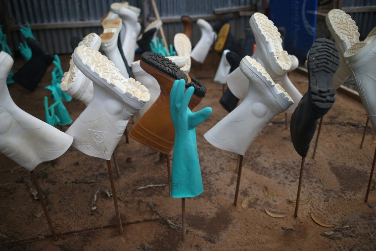 Sanitized gloves and boots hang to dry as a burial team collects Ebola victims from a Ministry of Health treatment center for cremation on October 2, 2014 in Monrovia, Liberia.