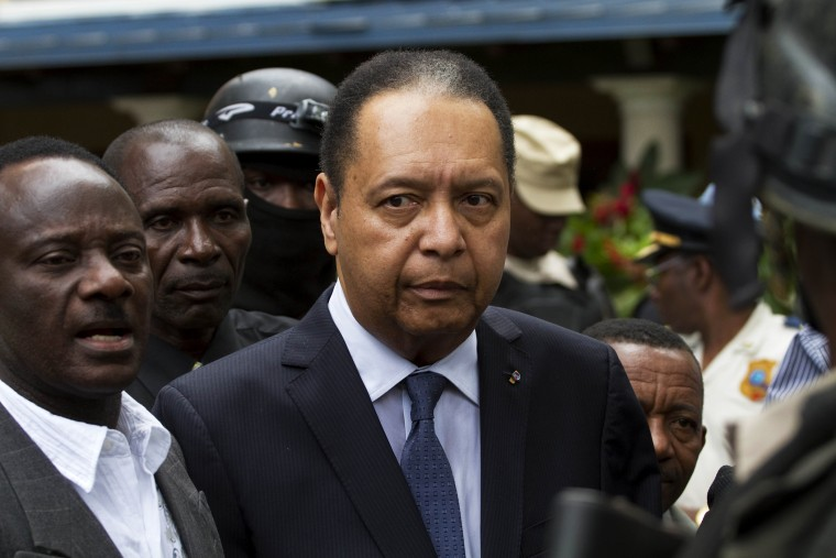 Haiti's ex-dictator Jean-Claude Duvalier is escorted out of his hotel in Port-au-Prince, Haiti Jan. 18, 2011. (Photo by Ramon Espinosa/AP)
