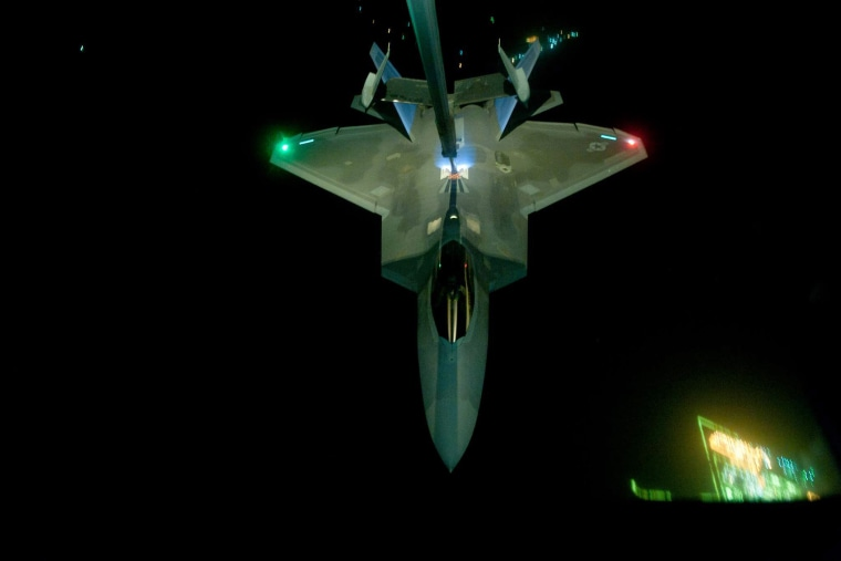 In this handout image provided by the U.S. Air Force, A KC-10 Extender refuels an F-22 Raptor fighter aircraft prior to strike operations in Syria, during flight on Sept. 26, 2014. (Photo by Tech. Sgt. Russ Scalf/U.S. Air Force /Getty)