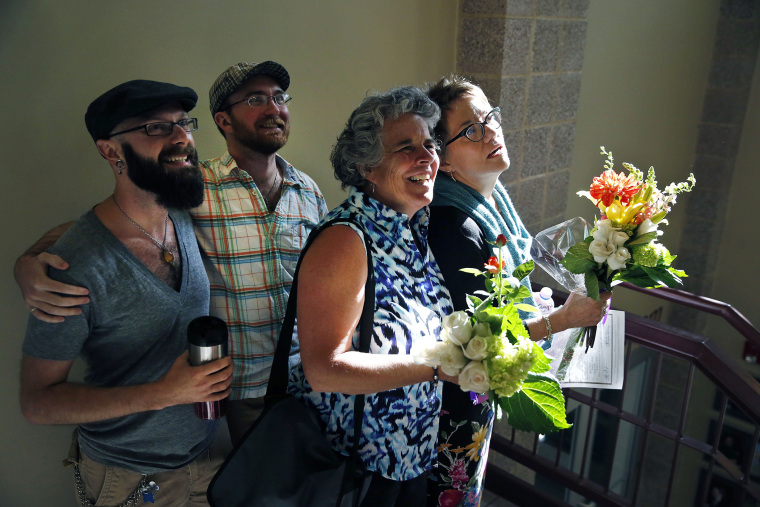 Same-sex couples Angie Holley, far right, and Bylo Farmer, and Levi Healy, far left, and Josh Hufford smile to friends as they depart the offices of the Boulder County Clerk and Recorder, in Boulder, Colo., on June 26, 2014.