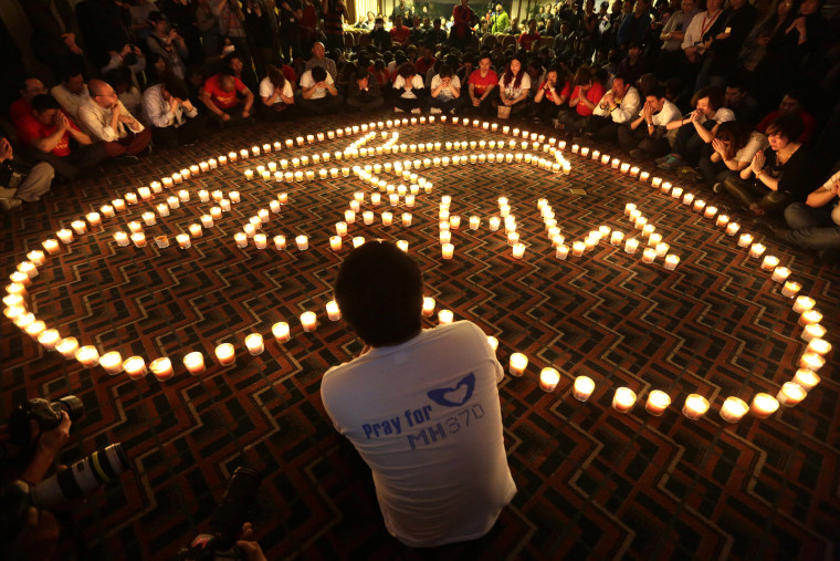 Relatives of passengers onboard Malaysia Airlines Flight MH370 pray during a candlelight vigil in the early morning, in Beijing on April 8, 2014. (Photo by Jason Lee/Reuters)