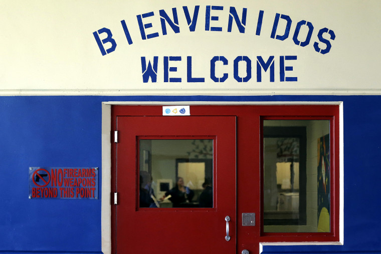 A Spanish and English welcome sign is seen above a door in a secured entrance area at the Karnes County Residential Center in Karnes City, Texas on July 31, 2014.