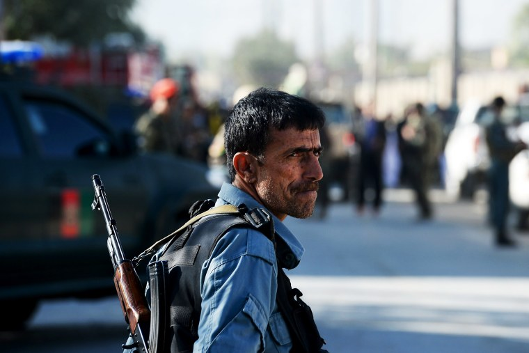 An Afghan policeman keeps watch at the site of a suicide attack in Kabul on October 2, 2014.
