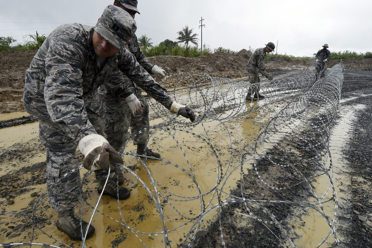 US Air Force soldiers place barbed wire in an area designated for a Ebola treatment center in Monrovia, on Oct. 6, 2014