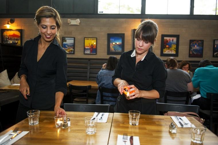 Kristin Ezell lights candles with Lydia Magoura at Mina's Mediterraneo, where she waitresses on May 16, 2014 in Miami Shores, Florida.