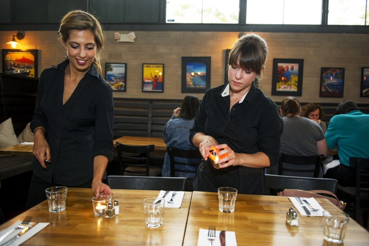 Kristin Ezell lights candles with Lydia Magoura at Mina's Mediterraneo, where she waitresses on May 16, 2014 in Miami Shores, Florida.