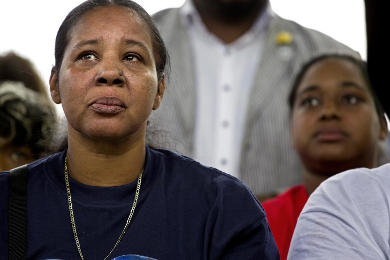 Esaw Garner, left, listens during remarks at a rally to protest the death of her husband Eric Garner, on Aug. 23, 2014, in the Staten Island borough of New York.